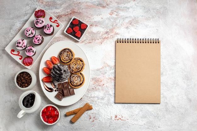 Вид сверху сладкое печенье с шоколадным тортом на белом фоне печенье бисквит сладкий торт сахарный чай