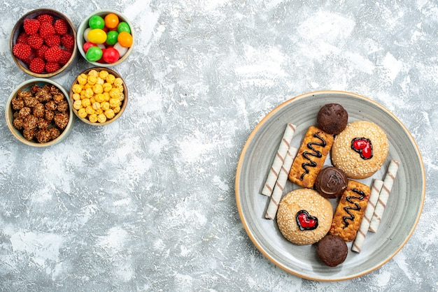 Вид сверху сладкое печенье с конфитюрами и орехами на белом фоне ореховые конфеты сахарное печенье сладкий торт пирог