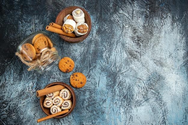 Vista dall'alto di biscotti dolci con confetture sulla superficie scura
