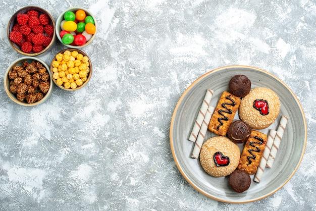 Vista dall'alto biscotti dolci con confitures e noci su sfondo bianco dado zucchero candito biscotto torta dolce torta