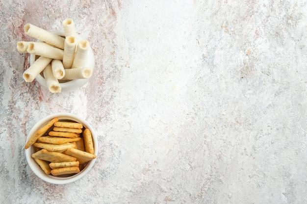 白いテーブルの上のクラッカーと甘いクッキーの上面図キャンディークッキーフルーツ