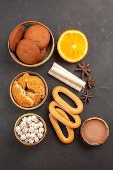 暗い背景のクッキービスケット甘いフルーツにクラッカーとトップビューの甘いクッキー