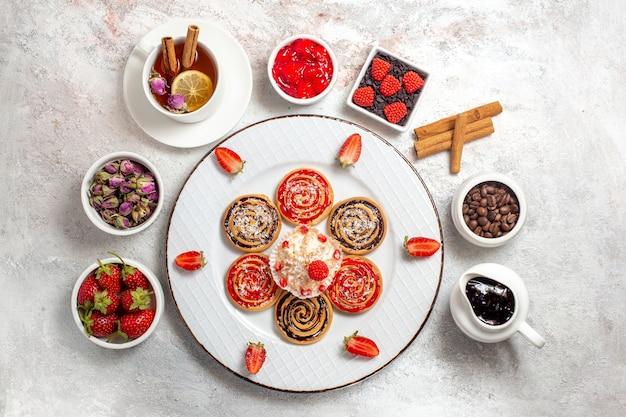 흰색 배경에 차 한잔과 함께 상위 뷰 달콤한 쿠키 달콤한 비스킷 차 케이크 쿠키 설탕