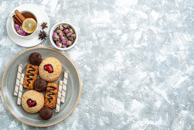 上面図白い背景にお茶と甘いクッキーナッツキャンディーシュガークッキー甘いケーキパイ
