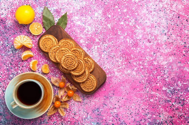 Top view of sweet cookies with cup of tea and citruses on pink surface