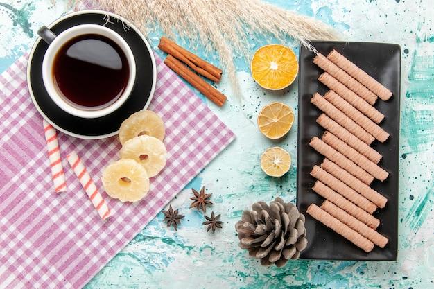 Vista dall'alto biscotti dolci con una tazza di tè e anelli di ananas essiccati su sfondo blu