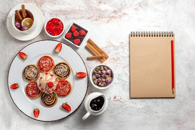 Biscotti dolci di vista superiore con la tazza di tè sullo zucchero del biscotto della torta del tè del biscotto dolce del fondo bianco