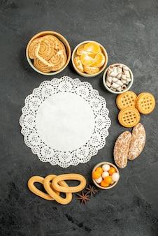 暗い机の上の果物とキャンディーのトップビューの甘いクッキークッキービスケット甘い