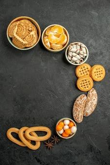 暗い机の上に果物やキャンディーと甘いクッキーの上面図