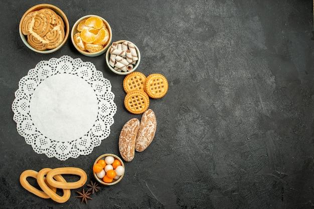 暗い床に果物やキャンディーと甘いクッキーの上面図