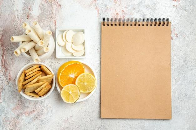 Вид сверху сладкое печенье с лимоном и крекерами на белом столе, печенье, сладкие фрукты, сахар