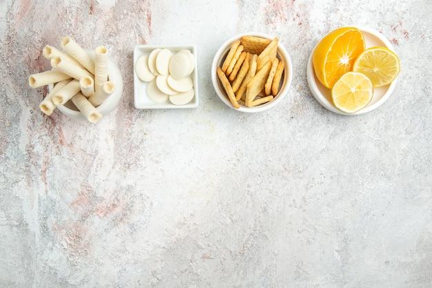 上面図白い床にレモンとクラッカーの甘いクッキービスケット甘いフルーツシュガー 無料写真