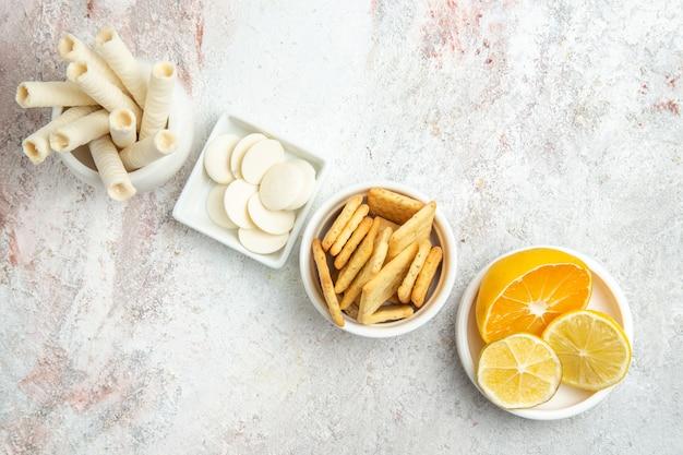 白いテーブルビスケットの甘いフルーツにレモンとクラッカーとトップビューの甘いクッキー