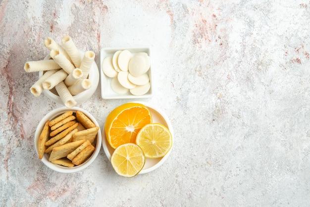 白いテーブルの上のレモンとクラッカーとトップビューの甘いクッキービスケット甘い果物砂糖