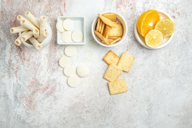 白いテーブルビスケットの甘い砂糖の果実にレモンとクラッカーとトップビューの甘いクッキー