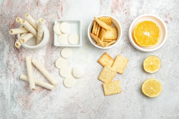 Biscotti dolci di vista superiore con limone e cracker sulla frutta zucchero dolce del biscotto della tavola bianca