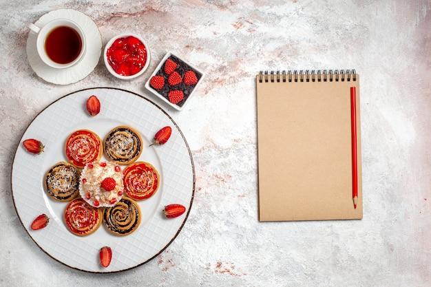 Vista dall'alto biscotti dolci con piccola torta e tazza di tè su uno sfondo bianco biscotto dolce tè torta di zucchero biscotto