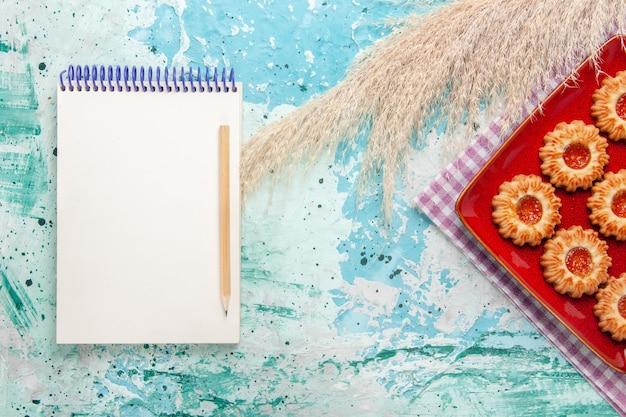 オレンジ色のジャムと青い背景のメモ帳とトップビューの甘いクッキー
