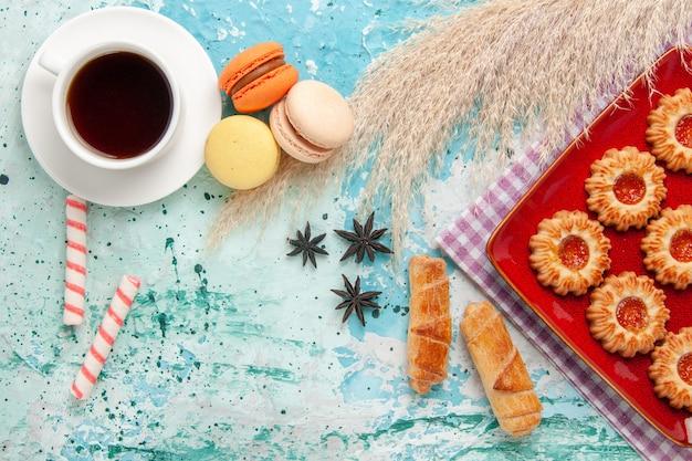オレンジ色のジャムベーグルと青い背景の上のお茶と甘いクッキーの上面図