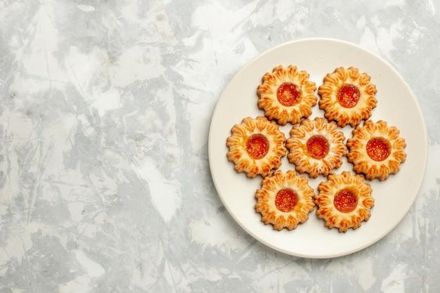 Biscotti dolci vista dall'alto con marmellata di arance su superficie bianca