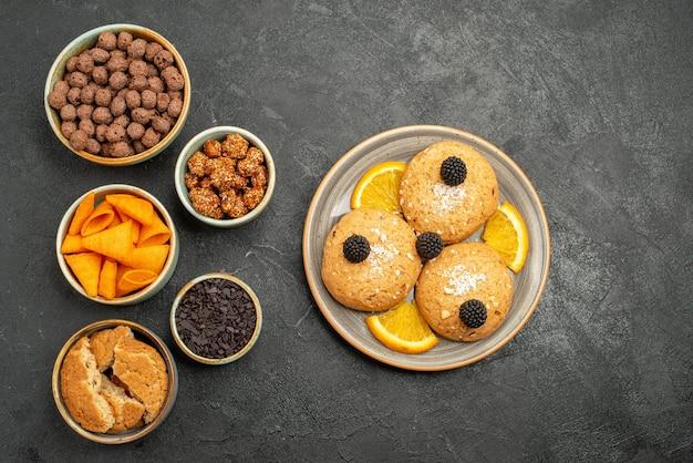 ダークグレーのバックグラウンドスナックビスケットクッキースウィートティーにオレンジスライスとチップスを添えた上面図スウィートクッキー