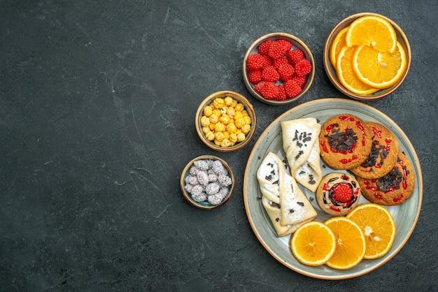 暗い表面のティービスケットの甘いクッキーケーキにペストリーオレンジスライスとキャンディーと上面図の甘いクッキー
