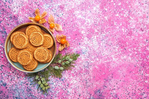 Vista dall'alto di biscotti dolci con fisalisi sulla superficie rosa chiaro