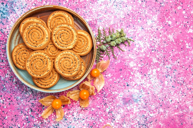 Top view of sweet cookies with physalises on pink surface
