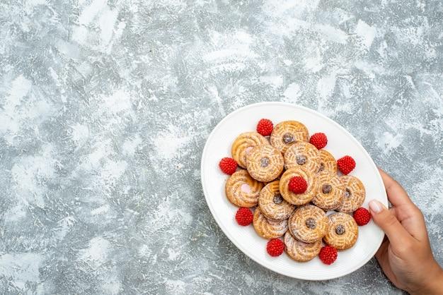 Вид сверху сладкое печенье с малиновыми конфитюрами внутри тарелки на белом фоне, печенье, сахар, бисквит, сладкий торт, чай