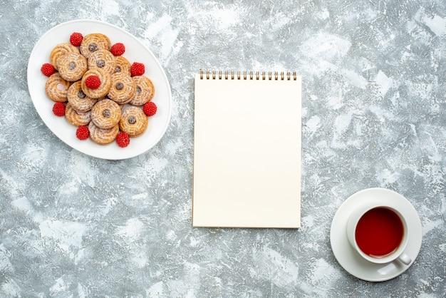 白い背景の上のプレートの内側にラズベリーのコンフィチュールが付いた上面図の甘いクッキーシュガービスケットの甘いケーキティー