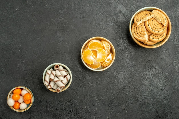 Вид сверху сладкое печенье с мандаринами на темном фоне