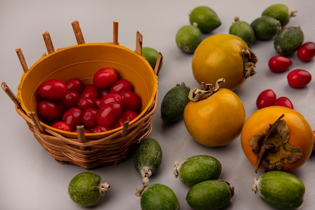 Vista dall'alto di ciliegie di corniola dolce su un secchio con feijoas e frutti di cachi isolati su un muro grigio