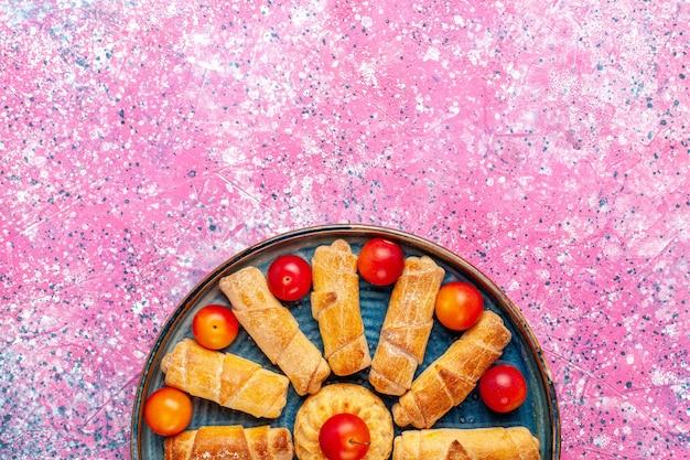 ピンクの机の上に梅とトレイの中のトップビュー甘いおいしいベーグル焼きペストリー