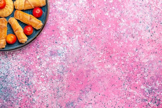 Вид сверху сладкие вкусные рогалики запеченные пирожные внутри подноса со сливами на розовой поверхности