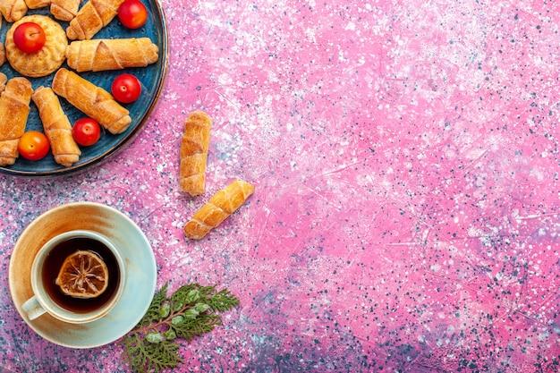 Вид сверху сладкие вкусные рогалики запеченные пирожные внутри подноса со сливами на розовом столе