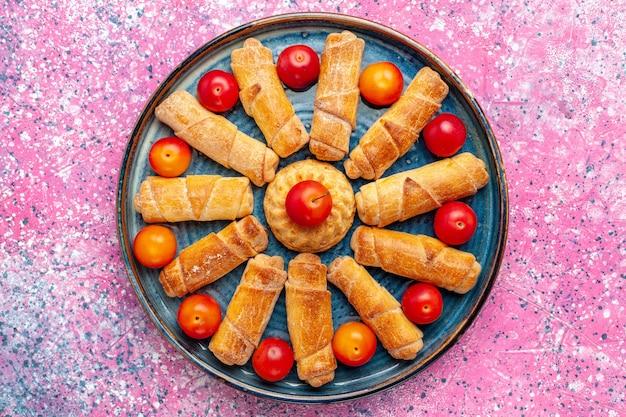 Вид сверху сладкие вкусные рогалики, запеченные кондитерские изделия внутри подноса на розовом столе