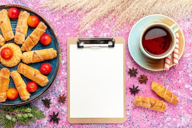 淡いピンクの机の上に新鮮なサワープラムとお茶が入ったトレイの中の甘いおいしいベーグルの上面図
