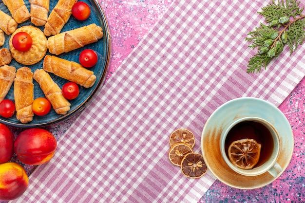 Вид сверху сладкие вкусные рогалики внутри подноса со сливами и персиками и чашкой чая на светло-розовом столе