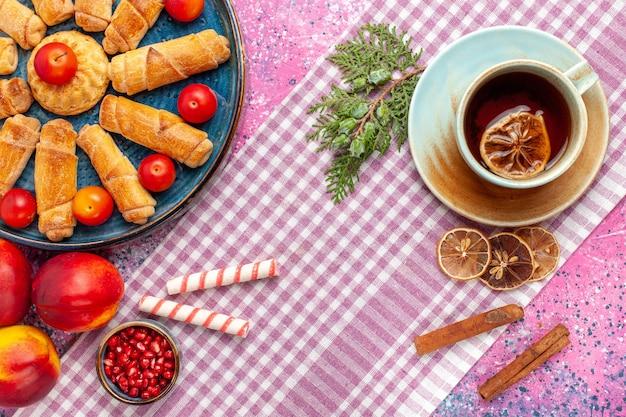 Vista dall'alto dolci deliziosi bagel all'interno del vassoio con prugne pesche e tazza di tè sulla scrivania rosa chiaro