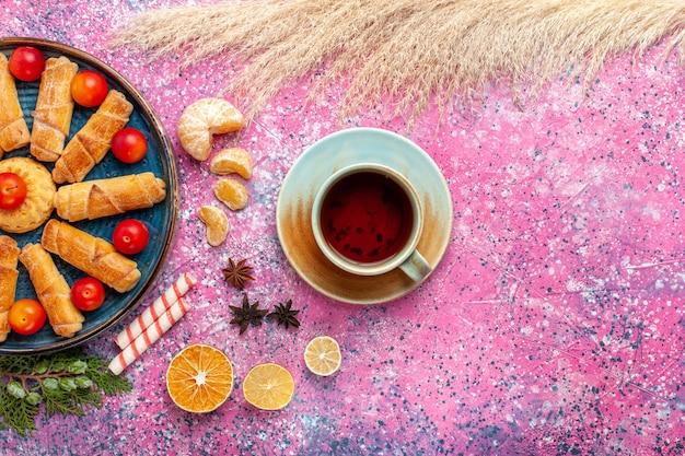 淡いピンクの机の上に酸っぱいプラムとお茶が入ったトレイの中の甘いおいしいベーグルの上面図