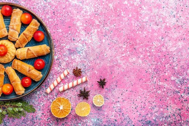 淡いピンクの机の上に酸っぱいプラムとトレイの中のトップビューの甘いおいしいベーグル