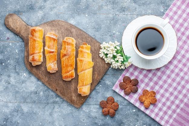 Vista dall'alto dolci deliziosi braccialetti con ripieno insieme a una tazza di biscotti al caffè sul tavolo in legno grigio dolce cuocere al forno pasticceria biscotto biscotto