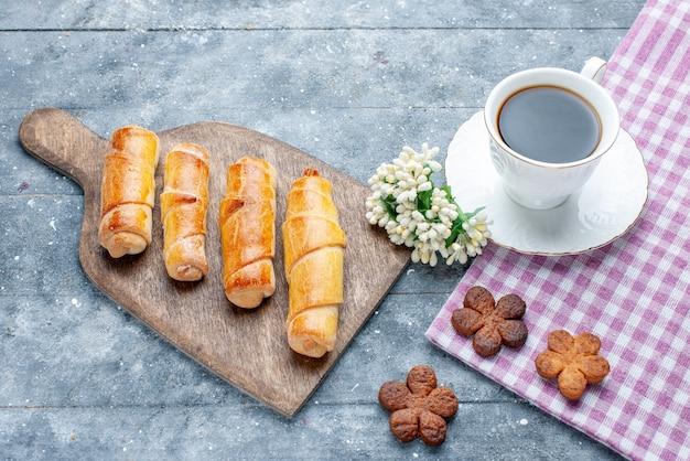 Vista dall'alto dolci deliziosi braccialetti con ripieno insieme a una tazza di caffè biscotti sul tavolo in legno grigio zucchero dolce cuocere al forno pasticceria biscotto biscotto