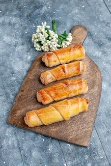 Вид сверху сладкие вкусные браслеты с начинкой на сером деревянном столе сладкая выпечка с сахаром, печенье, печенье