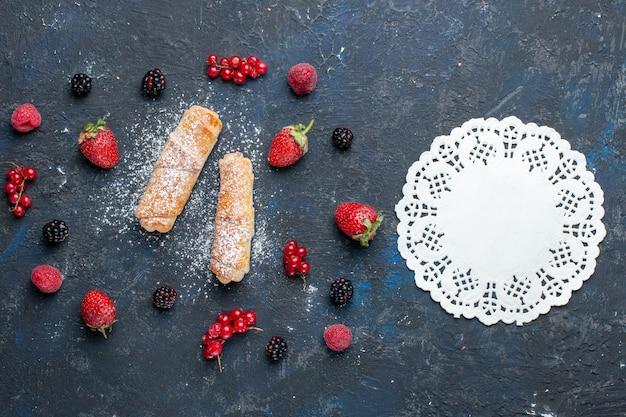 暗い背景にフルーツとベリーで焼いたおいしいフィリングと甘いおいしい腕輪を上から見たケーキを焼くビスケットシュガー甘いデザート