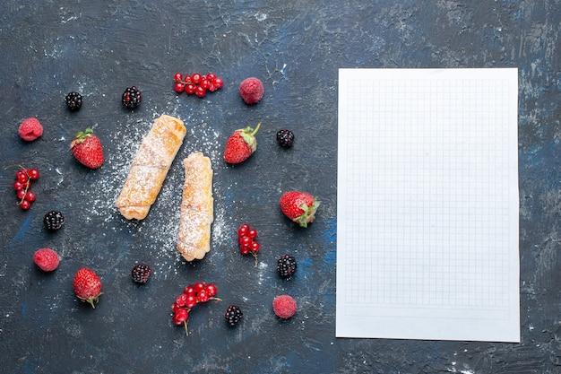 Vista dall'alto dolci deliziosi braccialetti con ripieno delizioso al forno con frutta e bacche di carta vuota sulla scrivania scura cuocere torta biscotto zucchero dolce dessert