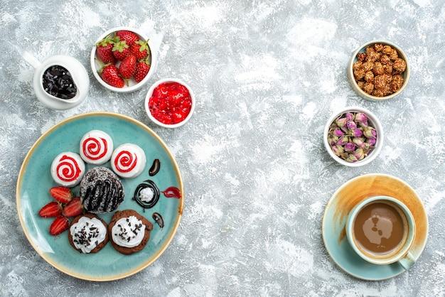 上面図白い背景の上のコーヒーのカップと甘いおいしいビスケットビスケットシュガーケーキクッキー甘い