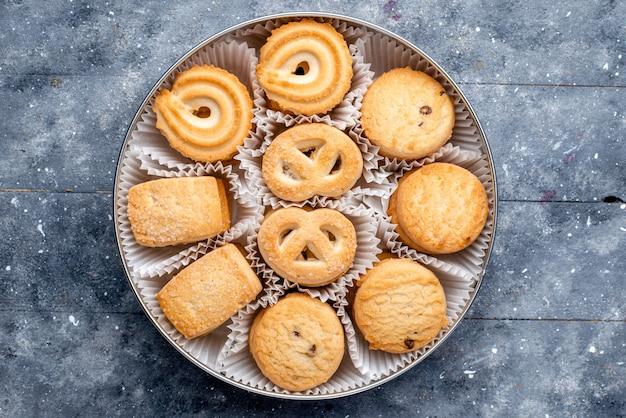 Vista dall'alto dolci deliziosi biscotti diversi formati all'interno del pacchetto rotondo sul biscotto di biscotto torta dolce zucchero grigio scrivania