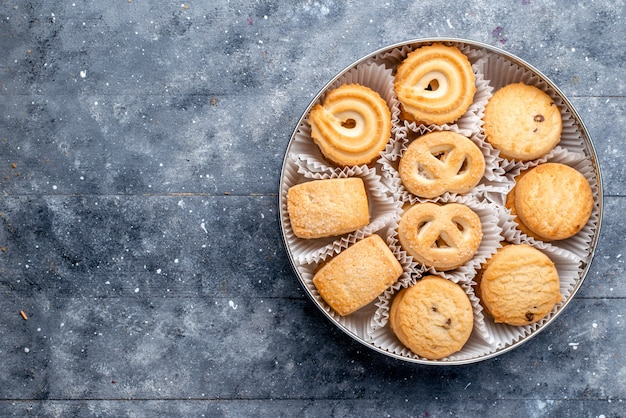 회색 책상에 둥근 패키지 안에 다른 모양의 달콤한 맛있는 쿠키 달콤한 케이크 비스킷 쿠키