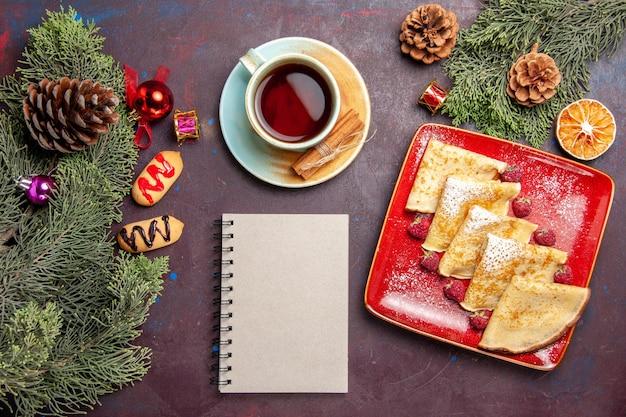 Vista dall'alto di deliziose frittelle dolci con una tazza di tè e lamponi su nero